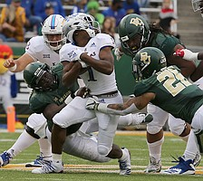 Kansas running back Pooka Williams Jr. (1) has his head turned on a penalty against a Baylor defender during the first half of an NCAA college football game, Saturday, Sept. 22, 2018, in Waco, Texas.