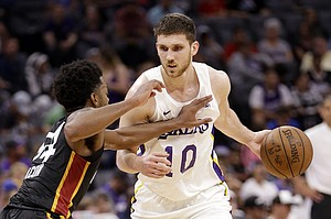 Los Angeles Lakers forward Sviatoslav Mykhailiuk, right, drives against Miami Heat guard Daryl Macon during the second half of an NBA summer league basketball game Tuesday, July 3, 2018, in Sacramento, Calif. (AP Photo/Rich Pedroncelli)