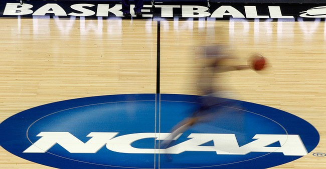 FILE - In this March 14, 2012, file photo, a player runs across the NCAA logo during practice in Pittsburgh before an NCAA tournament college basketball game. What some call the sleezy side of college basketball recruiting will be on display at a criminal trial starting Monday, Oct. 1, 2018, in New York. (AP Photo/Keith Srakocic, File)