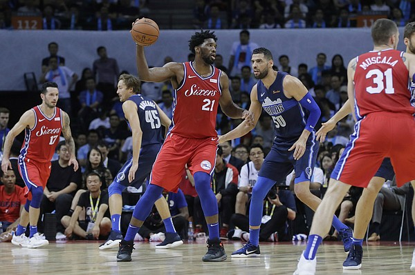 In this Oct. 8, 2018, file photo, Philadelphia 76ers' J.J. Redick (17), Dallas Mavericks' Ryan Broekhoff (45), of Australia, 76ers' Joel Embiid (21), of Cameroon, Mavericks' Salah Mejri (50), of Tunisia, 76ers' Mike Muscala (31) and Mavericks' Maxi Kleber, of Germany, play in an exhibition NBA basketball game in Shenzhen, China. (AP Photo/Kin Cheung, File)