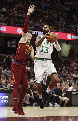 Boston Celtics' Marcus Morris (13) drives against Cleveland Cavaliers' Cedi Osman (16) in the first half of an NBA preseason basketball game, Saturday, Oct. 6, 2018, in Cleveland. (AP Photo/Tony Dejak)