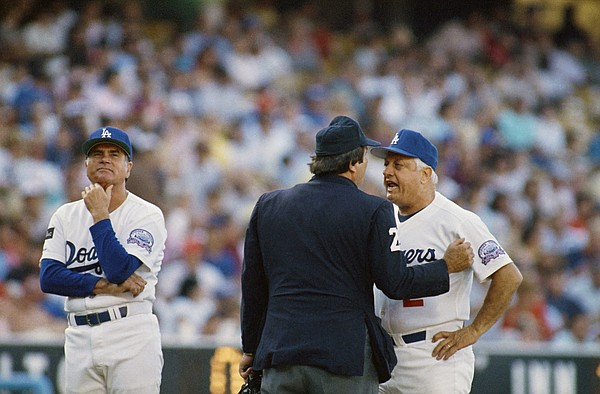 Los Angeles Dodgers third base coach Joe Amalfitano, left, waits while Dodgers manager Tommy Lasorda, right, argues with home plate umpire Fred Brocklander about a call during second inning action with the Cincinnati Reds, Tuesday, Aug. 12, 1987, Los Angeles, Calif. Lasorda continued arguing but to no avail as the ump stood his ground until Lasorda headed back to the dugout. The Dodgers won the game 7-2 anyway. (AP Photo/Lennox McLendon)