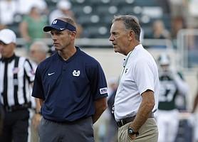 Utah State coach Matt Wells, left, and Michigan State coach Mark Dantonio talk before an NCAA college football game, Friday, Aug. 31, 2018, in East Lansing, Mich. (AP Photo/Al Goldis)