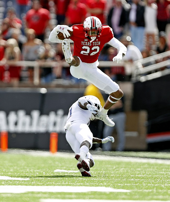 Texas Tech's Seth Collins (22) leaps over Kansas' Mike Lee (11) during the first half of an NCAA college football game Saturday, Oct. 20, 2018, in Lubbock, Texas.