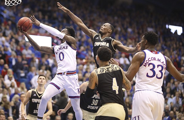 Kansas guard Marcus Garrett (0) swoops to the bucket past Emporia State forward Hassan Thomas (3) during the first half of an exhibition, Thursday, Oct. 25, 2018 at Allen Fieldhouse.