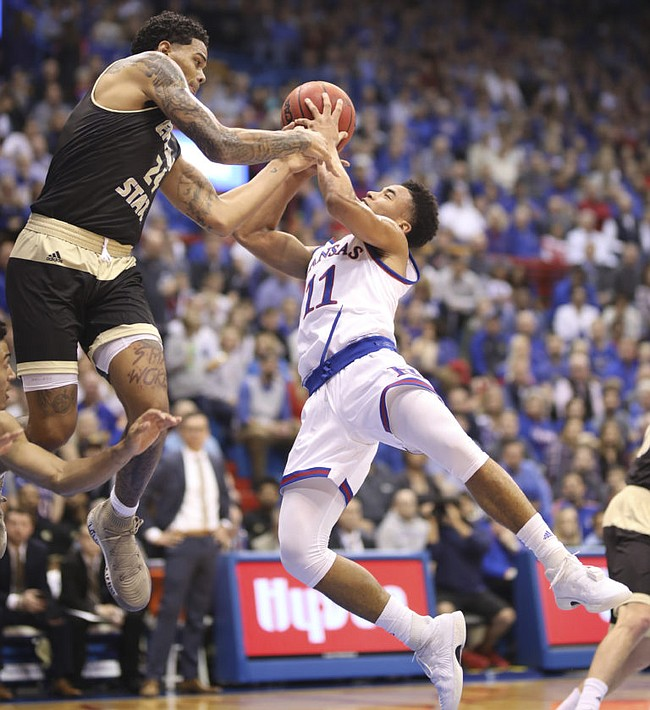 Kansas guard Devon Dotson (11) tangles with Emporia State forward Justin Washington (24) during the first half of an exhibition, Thursday, Oct. 25, 2018 at Allen Fieldhouse.
