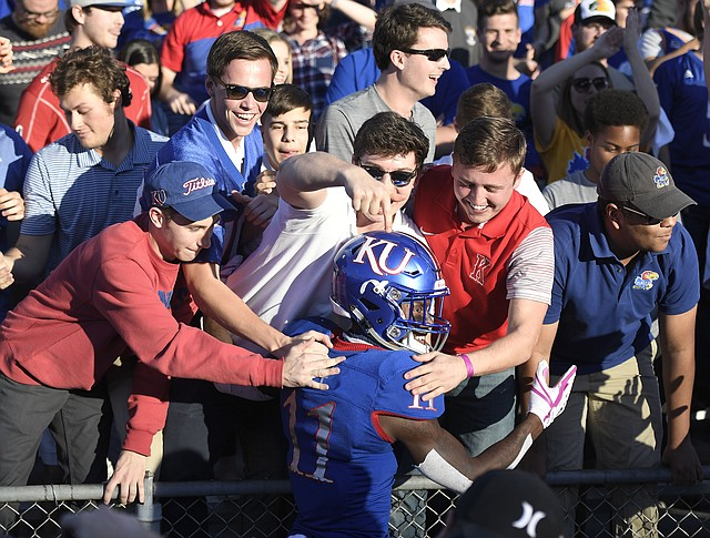 Kansas safety Mike Lee celebrated with fans after the win against TCU.