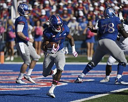 Pooka Williams runs through the TCU defense Saturday at David Booth Kansas Memorial Stadium. The Jayhawks claimed a 27-26 win over the Horned Frogs, which ended their 14-game skid in league play.