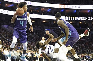 Charlotte Hornets' Devonte' Graham (4) picks up a loose ball as Philadelphia 76ers' Joel Embiid (21) falls to the floor in the second half of an NBA basketball game, Saturday, Oct. 27, 2018, in Philadelphia. The 76ers defeated the Hornets 105-103. (AP Photo/Michael Perez)