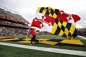 A cheerleader carries a Maryland flag across the field in the first half of an NCAA college football game against Illinois, Saturday, Oct. 27, 2018, in College Park, Md. (AP Photo/Patrick Semansky)