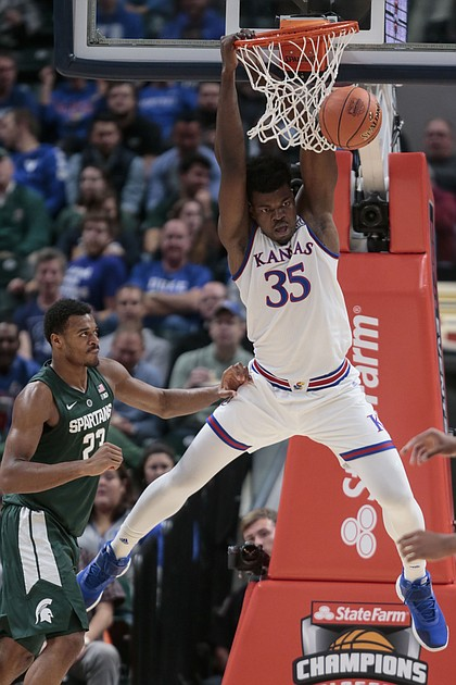 Kansas center Udoka Azubuike (35) dunks in front of Michigan State forward Xavier Tillman during the first half of an NCAA college basketball game at the Champions Classic on Tuesday, Nov. 6, 2018, in Indianapolis.