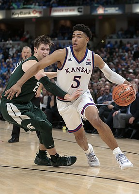 Kansas guard Quentin Grimes (5) goes around Michigan State guard Matt McQuaid (20) in the second half of an NCAA college basketball game at the Champions Classic on Tuesday, Nov. 6, 2018, in Indianapolis. Kansas won. 92-87.