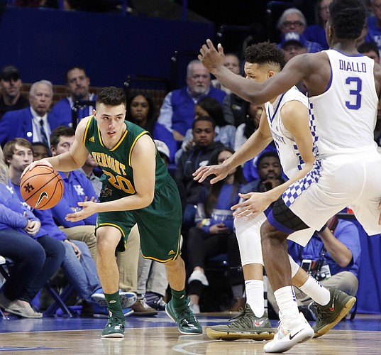 Vermont's Ernie Duncan, left, looks for an opening against Kentucky's Kevin Knox and Hamidou Diallo (3) during the second half of an NCAA college basketball game, Sunday, Nov. 12, 2017, in Lexington, Ky.
