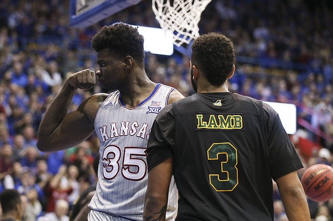 Kansas center Udoka Azubuike (35) flexes after a dunk before Vermont forward Anthony Lamb (3) during the first half, Monday, Nov. 12, 2018 at Allen Fieldhouse.