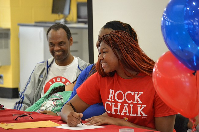 Lawrence High senior Chisom Ajekwu signs her national letter of intent Friday afternoon at LHS. Ajekwu is committed to play for KU women's basketball team at the collegiate level.