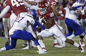 Oklahoma running back Kennedy Brooks (26) runs as Kansas safety Mike Lee (11) defends during the first half of an NCAA college football game in Norman, Okla., Saturday, Nov. 17, 2018. (AP Photo/Alonzo Adams)