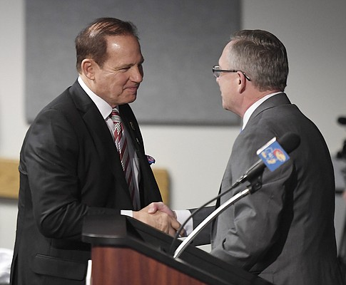 University of Kansas Athletic Director Jeff Long, right, and new football coach Les Miles shake hands during a press conference Sunday, Nov. 18, 2018, at Hadl Auditorium.