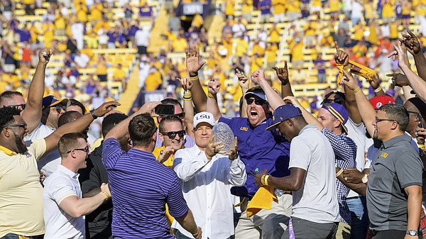 FILE — Former LSU head coach Les Miles, center, is mobbed by LSU football alumni of the 2007-8 BCS National Championship team during a halftime ceremony in an NCAA college football game against Auburn in Baton Rouge, La., Saturday, Oct. 14, 2017. Miles became the incoming head coach at the University of Kansas on Nov. 18, 2018. (AP Photo/Matthew Hinton)