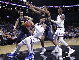 Kansas' Dedric Lawson (1) looks to pass away from Marquette's Matt Heldt (12) and Joey Hauser as teammate Marcus Garrett, right, watches during the first half of an NCAA college basketball game in the NIT Season Tip-Off tournament Wednesday, Nov. 21, 2018, in New York.