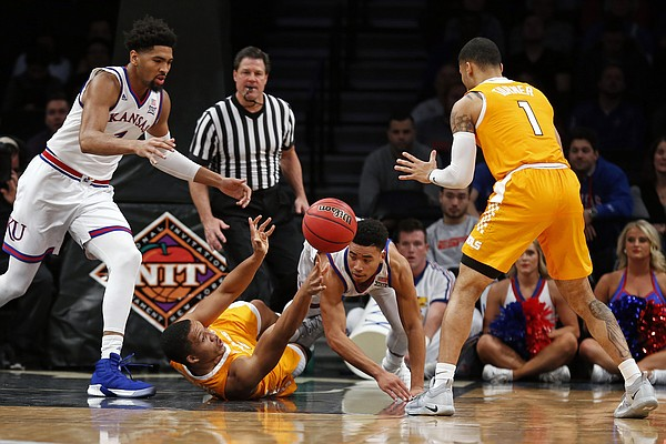 Tennessee forward Grant Williams passes the ball to Lamonte Turner, right, as Kansas forward Dedric Lawson, left, and guard Devon Dotson defend during the first half of an NCAA college basketball game in the NIT Season Tip-Off tournament Friday, Nov. 23, 2018, in New York. (AP Photo/Adam Hunger)