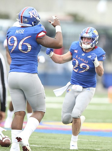 Kansas linebacker Joe Dineen Jr. (29) bemoans a missed interception with teammate Kansas defensive tackle Daniel Wise (96) during the first quarter on Friday, Nov. 23, 2018 at Memorial Stadium.