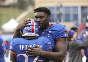 Kansas offensive lineman Hakeem Adeniji (78) hugs Kansas running back Deron Thompson (26) as time runs out in the fourth quarter on Friday, Nov. 23, 2018 at Memorial Stadium.