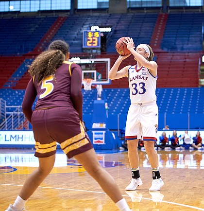 Kansas guard Kylee Kopatich (33) shoots a 3-pointer as Iona's Shyan Mwai (5) looks on in the first quarter on Sunday, Nov. 25, 2018 at Allen Fieldhouse.