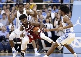 North Carolina's Kenny Williams, rear, and Coby White guard Stanford's Daejon Davis (1) during the first half of an NCAA college basketball game in Chapel Hill, N.C., Monday, Nov. 12, 2018. (AP Photo/Gerry Broome)
