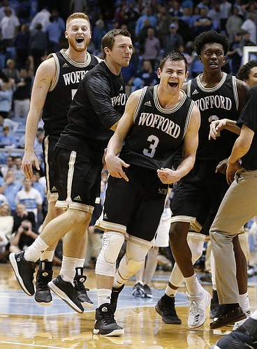 Wofford players, including Fletcher Magee (3), Matthew Pegram, left rear, and Michael Manning Jr., right rear, celebrate the team's 79-75 win over North Carolina in an NCAA college basketball game in Chapel Hill, N.C., Wednesday, Dec. 20, 2017. (AP Photo/Ellen Ozier)
