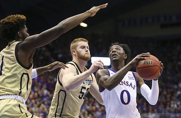 Kansas guard Marcus Garrett (0) moves to the bucket past Wofford center Matthew Pegram (50) during the second half on Tuesday, Dec. 4, 2018 at Allen Fieldhouse.