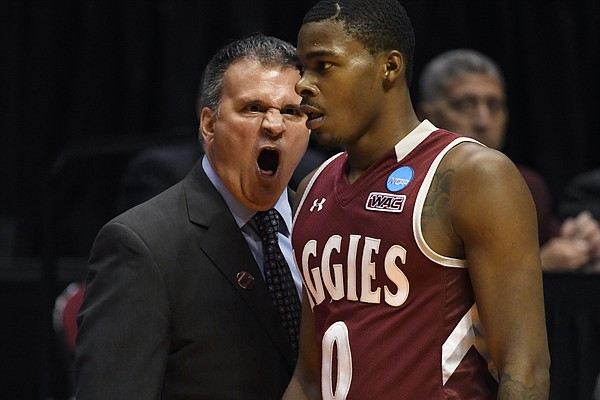 New Mexico State head coach Chris Jans, left, has a word with New Mexico State guard Keyon Jones (0) during the first half of a first-round NCAA college basketball tournament game against Clemson, Friday, March 16, 2018, in San Diego. (AP Photo/Denis Poroy)
