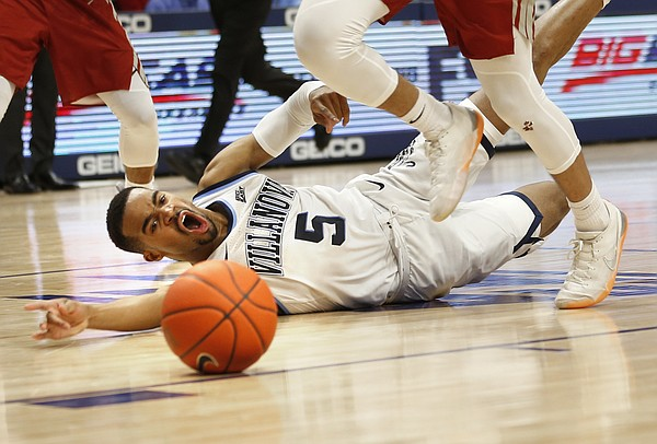 Villanova guard Phil Booth (5)] is tripped up by Saint Joseph's guard Jared Bynum (3) during the second half of an NCAA college basketball game, Saturday, Dec. 8, 2018, in Villanova, Pa. Villanova won 70-58. (AP Photo/Laurence Kesterson)