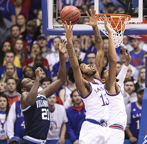Kansas guard K.J. Lawson (13) grabs a rebound over Villanova forward Dhamir Cosby-Roundtree (21) during the first half, Saturday, Dec. 15, 2018 at Allen Fieldhouse.