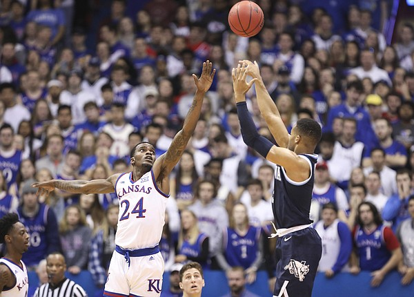 Villanova guard Phil Booth (5) puts up a three over Kansas guard Lagerald Vick (24) during the first half, Saturday, Dec. 15, 2018 at Allen Fieldhouse.