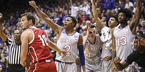 Kansas guard Charlie Moore (2) hangs his hand in the air after putting up a three from the corner over South Dakota guard Cody Kelley (10) as the bench celebrates during the second half, Tuesday, Dec. 18, 2018 at Allen Fieldhouse.
