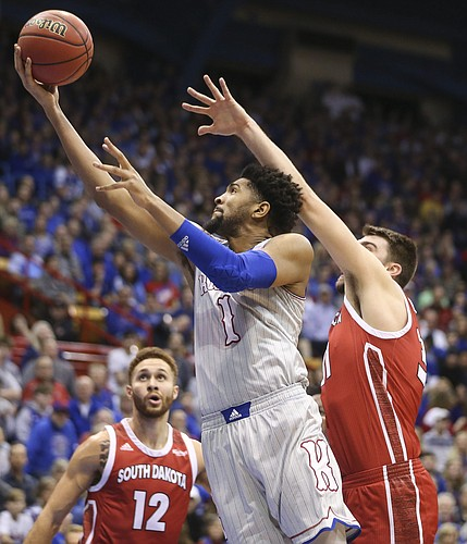 Kansas forward Dedric Lawson (1) squeezes in for a bucket past South Dakota forward Dan Jech (31) during the first half, Tuesday, Dec. 18, 2018 at Allen Fieldhouse.