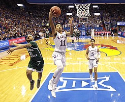 Kansas' Devon Dotson (11) gets past Eastern Michigan's Malik Ellison (10) to put up a shot during the first half of an NCAA college basketball game Saturday, Dec. 29, 2018, in Lawrence, Kan.