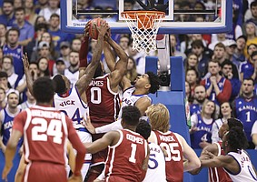 Kansas forward Dedric Lawson (1) and Kansas guard Lagerald Vick (24) stuff a shot attempt from Oklahoma guard Christian James (0) during the first second, Wednesday, Jan. 2, 2019 at Allen Fieldhouse.