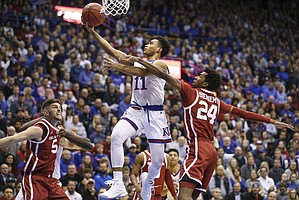 Kansas guard Devon Dotson (11) cruises in for a bucket past Oklahoma guard Jamal Bieniemy (24) during the first half, Wednesday, Jan. 2, 2019 at Allen Fieldhouse.