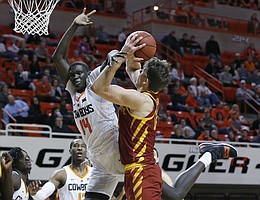 Iowa State forward Michael Jacobson (12) is fouled by Oklahoma State forward Yor Anei (14) during the second half of an NCAA college basketball game in Stillwater, Okla., Wednesday, Jan. 2, 2019. (AP Photo/Sue Ogrocki)