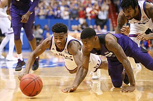 Kansas guard Ochai Agbaji (30) gets on the floor for a ball with TCU guard Kendric Davis (5) during the second half, Wednesday, Jan. 9, 2019 at Allen Fieldhouse.