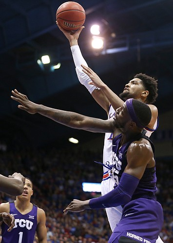 Kansas forward Dedric Lawson (1) gets in for a bucket over TCU forward JD Miller (15) during the second half, Wednesday, Jan. 9, 2019 at Allen Fieldhouse.