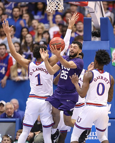TCU guard Alex Robinson (25) tosses a shot over his head after running out of options against Kansas forward Dedric Lawson (1) and Kansas guard Marcus Garrett (0) during the first half, Wednesday, Jan. 9, 2019 at Allen Fieldhouse.