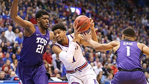 Kansas forward Dedric Lawson (1) drives against TCU center Kevin Samuel (21) and TCU guard Desmond Bane (1) during the first half, Wednesday, Jan. 9, 2019 at Allen Fieldhouse.