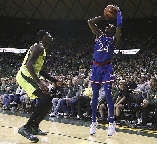 Kansas guard Lagerald Vick (24) shoots a three-point shot over Baylor guard Mario Kegler (4) in the second half of an NCAA college basketball game, Saturday, Jan. 12, 2019, in Waco, Texas. (AP Photo/Jerry Larson)