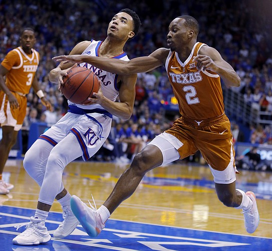 Texas guard Matt Coleman III (2) tries to steal the ball from Kansas guard Devon Dotson (11) during the first half of an NCAA college basketball game Monday, Jan. 14, 2019, in Lawrence, Kan. (AP Photo/Charlie Riedel)