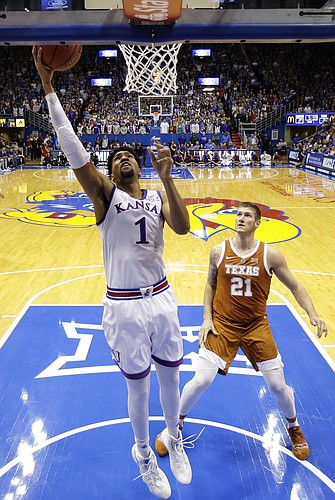 Kansas forward Dedric Lawson (1) gets past Texas forward Dylan Osetkowski (21) to put up a shot during the first half of an NCAA college basketball game Monday, Jan. 14, 2019, in Lawrence, Kan. (AP Photo/Charlie Riedel)