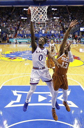 Kansas guard Marcus Garrett (0) gets past Texas guard Jase Febres (13) to put up a shot during the first half of an NCAA college basketball game Monday, Jan. 14, 2019, in Lawrence, Kan. (AP Photo/Charlie Riedel)