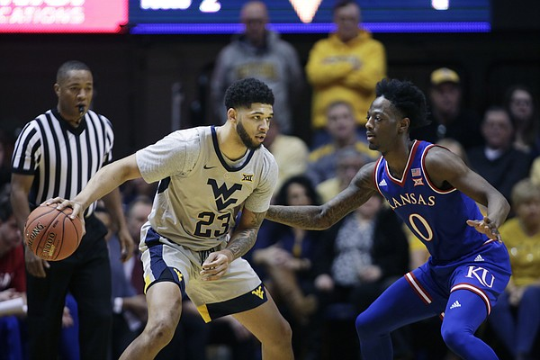 West Virginia forward Esa Ahmad (23) looks to make a pass while defended by Kansas guard Marcus Garrett (0) during the first half of an NCAA college basketball game Saturday, Jan. 19, 2019, in Morgantown, W.Va.