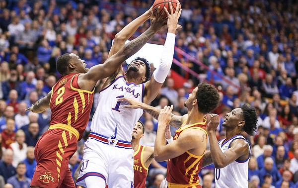 Kansas forward Dedric Lawson (1) grabs an offensive rebound over Iowa State forward Cameron Lard (2) and Iowa State guard Nick Weiler-Babb (1) during the first half, Monday, Jan. 21, 2019 at Allen Fieldhouse. At right is Kansas guard Marcus Garrett (0).